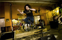 Fourteen-year-old frontman Colin Phillips jumps through the air as his band, Ragged Stagger, performs at Plano&#039;s Eisenbergs Skatepark on Friday, March 28.