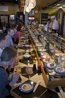 Covered dishes of sushi march past on Genki&#039;s conveyor belt, a sort of perpetual eating machine.