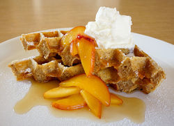 Oatmeal waffle with mascarpone cream, warm peaches, pure maple syrup and butter.