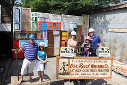 The scrap-metal business on Rock Island is a longtime family affair. Here, from left, are John Hargrove and his daughter Hannah of Orr-Reed Wrecking, Frances Okon, her granddaughter Toni and son Louis of Okon Metals. The gates at Orr-reed, made of salvaged doors, are the work of artist Cydney Ferguson.