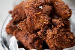 Sissy&#039;s bucket of fried chicken pairs well with an overstuffed couch.