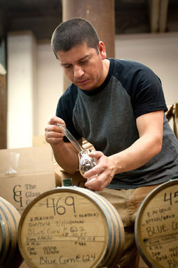 Employee at Waco&amp;#146;s Balcones Distilling plant tests a whiskey sample.