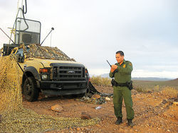 A Border Patrol surveillance truck sits camouflaged atop a hill in southeastern Arizona.