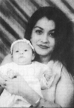 Beautiful Sigreda Fernandez, assassinated by Smiley to keep her quiet, holds their baby.