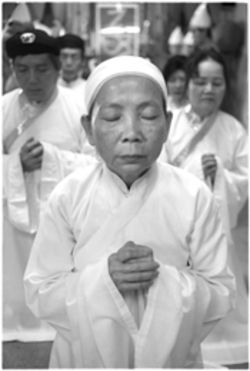 Muoi Huong Le, priestess of the Cao Dai Tay Ninh Temples of Texas, Mountain View, stands in front of the faithful and prays during a temple service. Le vowed never to return to her homeland after Vietnamese officials detained her for possessing a book of Cao Dai doctrine not sanctioned by the communist government.