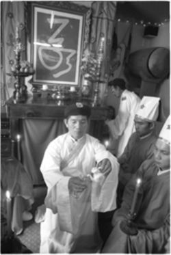 Quan Phuoc Bui pours tea as an offering to God during a temple service in Mountain View.
