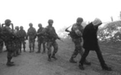 U.S. soldiers in Macedonia detain an ethnic Albanian villager suspected of aiding the NLA. Many of the Albanian soldiers fighting the Serbs in Kosovo were from Macedonia and have returned to destabilize their homeland, putting them at odds with their former U.S. allies.