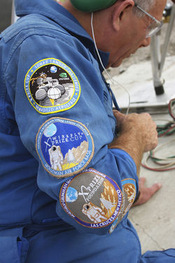 Armadillo engineer Neil Milburn in a team jumpsuit decked out in patches from past X Prize Cup events in which Armadillo has competed